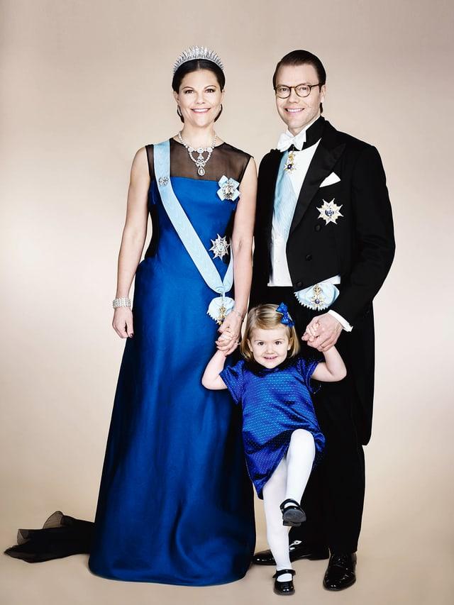 DIe Schwedischekranprinzenfamilie. Kronprinzessin Victoria im bodenlangen. blauen Kleid. Prinz Daniel trägt einen eleganten schwarzen Frack. Die kleine Etselle trägt auch ein blaues Kleid und will nicht so richtig stillstehen.