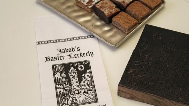 Läckerli, eine Papiertüte und ein Holzschnitt