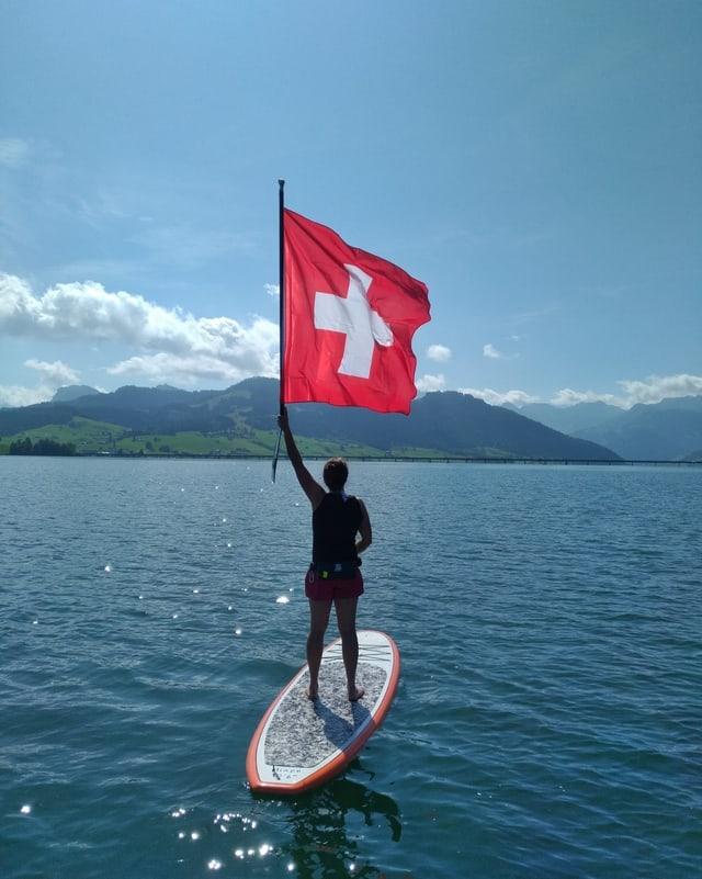 Surferin auf See mit Schweizer Fahne.