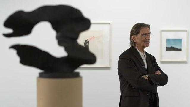 ein Mann steht hinter einer Skulptur