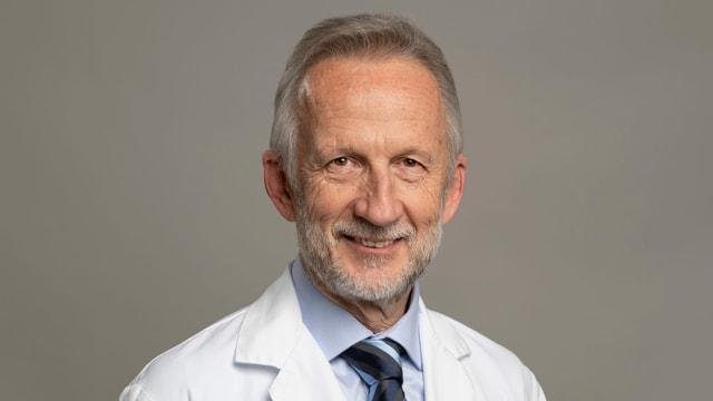 Arzt im weissen Kittel mit grauen, kurzen Haaren