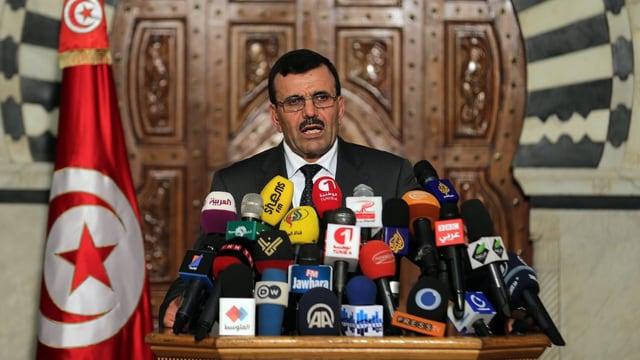Larayedh vor Mikrofonen, flankiert von der tunesischen Flagge, kündigt Neuwahlen an.