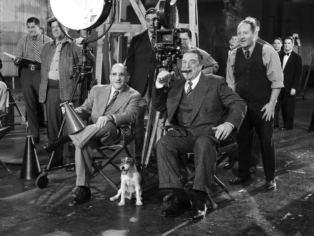 Szenen eines Drehs in Hollywood mit Kameramann, Regisseur und Assistenten. Ein zwei Männer sitzen in Vordergrund. Einer mit Zigarre im Mund, einer mit Megafon in der Hand. zu ihren Füssen sitzt ein kleiner, heller Hund.
