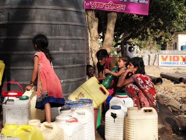 Drei Mädchen hocken um leere Wasserkanister. Eines steht.