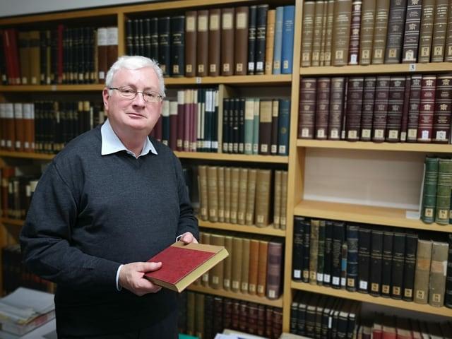 Mann vor einer Bücherwand.