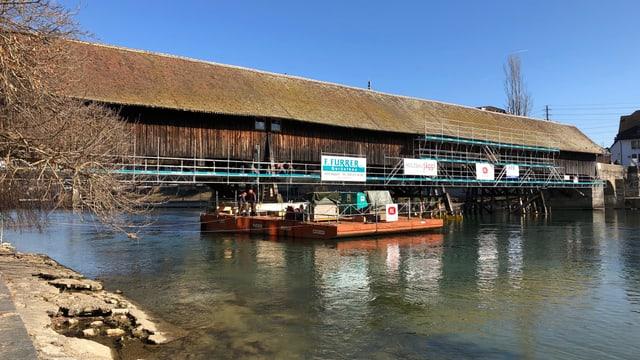 Blick auf die Holzbrücke von der Altstadt-Seite aus. In der Mitte des Bildes liegt der orange Schwimmkörper in der Aare vor der Brücke.