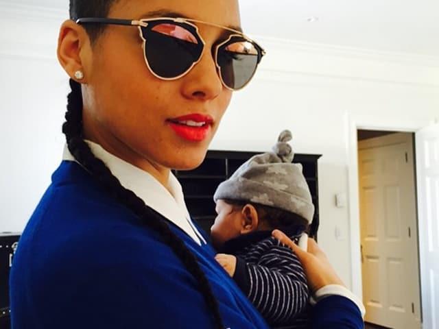 Alicia Keys mit Sonnenbrille. Sie trägt ihr Baby mit grauer Mütze auf dem Arm.