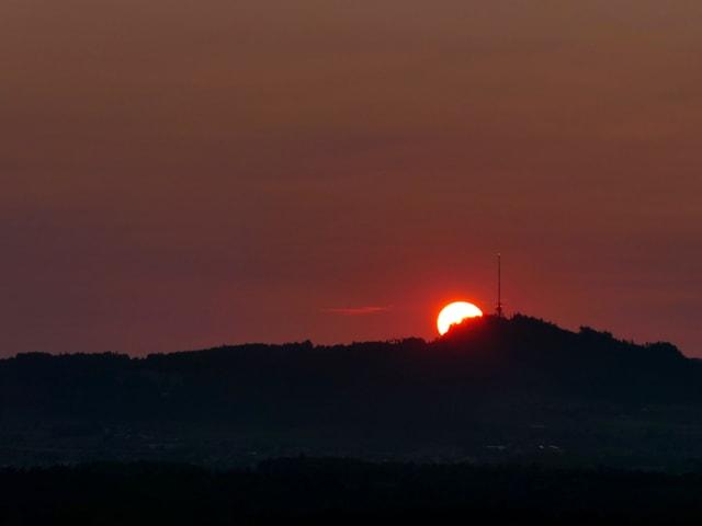 Neben dem Sendemast am Bantiger geht die Sonne auf, der Himmel ist dunkelrot verfärbt.