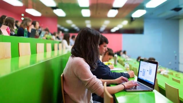 Studenten in einem Vorlesungssaal. Eine Frau schreibt auf einem Laptop. Die Bänke sind grün.