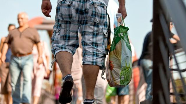 Ein Mann trägt im Grenzort Konstanz eine Einkaufstasche.