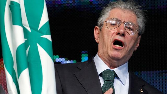 Bossi mit Brille neben einer Flagge.