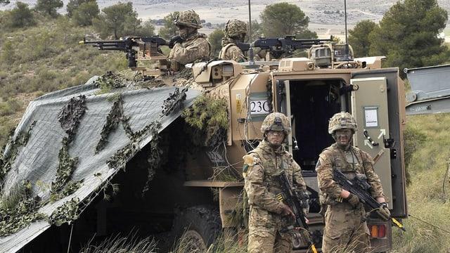 Bewaffnete Soldaten in Tarnanzügen stehen um ein gepanzertes Fahrzeug.