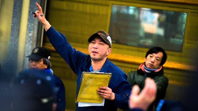Ein Auktionator mit Mütze streckt den Zeigefinger in die Höhe.