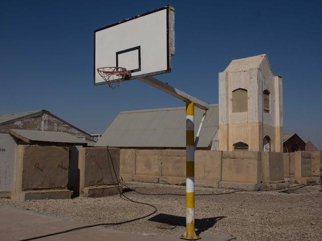 Ein Basketballkorb und im Hintergrund eine einfache Kirche.