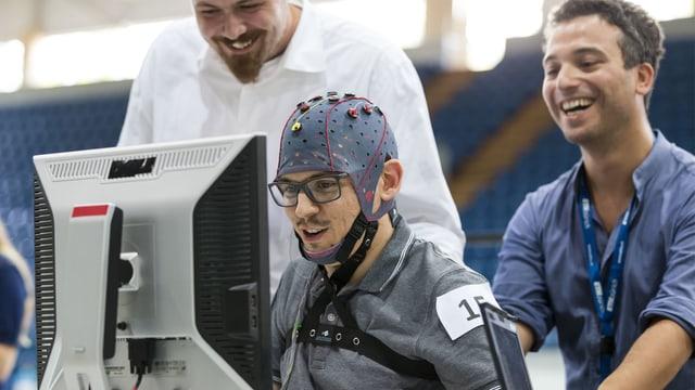 Ein Mann mit einer Elektrodenhaube auf dem Kopf sitzt vor einem Computerbildschirm