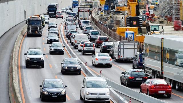 viele Autos auf Autobahn, gelbe Baukranen