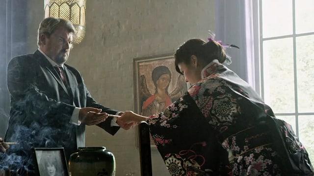 Japanisches Trauerritual: Eine Frau im Kimono reicht einem Mann die Stäbchen, ein junger, dunkel gekleideter Mann schaut ihnen dabei zu.