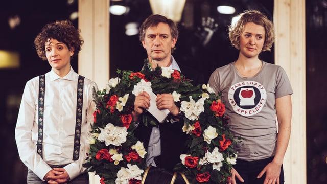 Zwei Frauen - in der Mitte ein Mann. Er hat einen Blumenkranz in der Hand. Die Angst wird beerdigt.