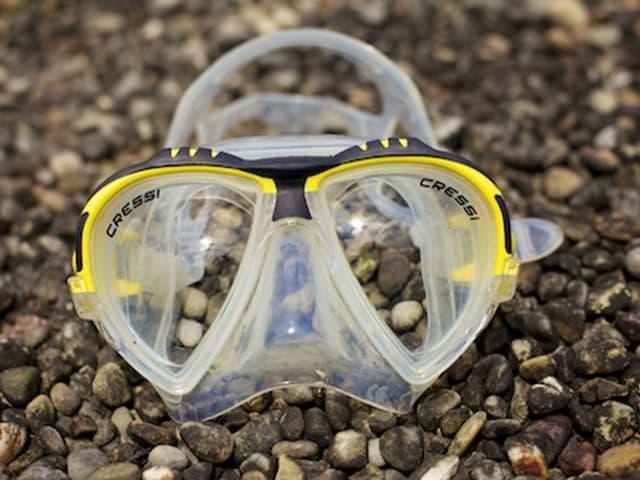 Eine Taucherbrille liegt auf einem Kiesboden.