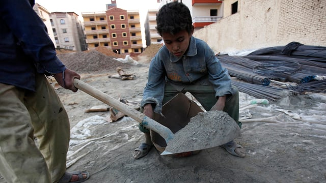 Ein Junge mit einem Zementeimer
