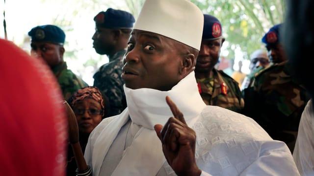 Jammeh in Weiss blickt in die Kamera mit erhobenem Zeigfinger.