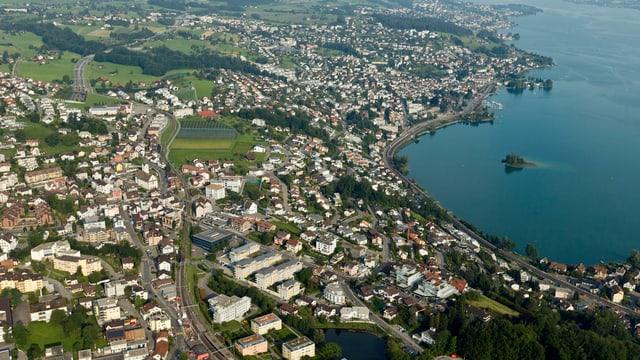 Ein Dorf an einem See gelegen (Luftaufnahme).