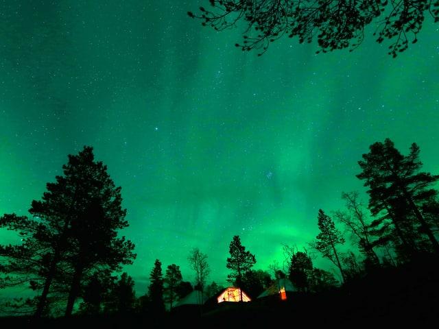 Hinter einem warm leuchtenden Haus und einigen Bäumen tut sich ein Himmel voll grünem Polarlicht auf.
