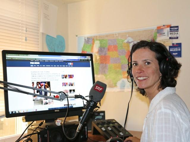 Korrespondentin in ihrem Büro mit Mikrofon und Bildschirm.