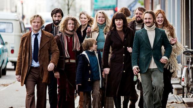 11 Menschen verschiedenen Alters, die lachend einen Gehsteig entlang gehen.