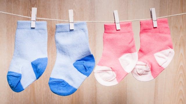 Ein Paar blaue und ein Paar rosa Socken hängen an einer Wäscheleine.