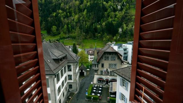 Blick auf das Urner Rathaus und den Berghang.