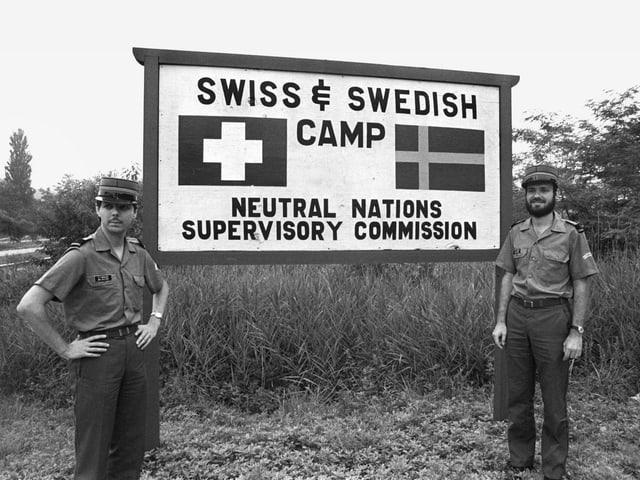 Zwei Soldaten stehen vor einem Schild mit der Aufschrift «Swiss & Swedish camp».