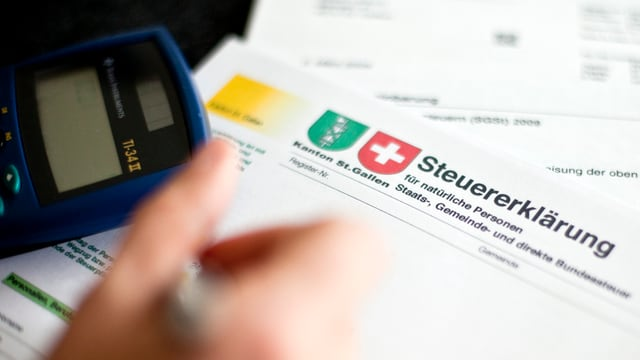 Ein Taschenrechner und eine Hand mit einem Kugelschreiber über einer Steuererklärung.
