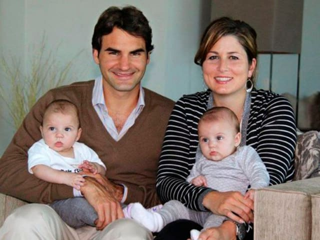 Mirka und Roger Federer mit Myla und Charlene im Arm auf einem Sofa sitzend.