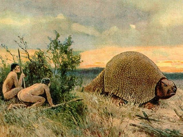 Zwei Menschen hocken hinter einem Buch und lauern einem Glyptodon auf.