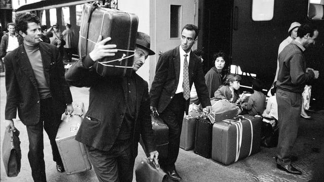 Männer tragen Koffern durch den Bahnhof