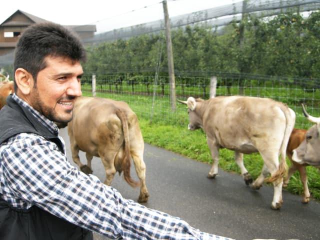 Ein Mann steht lächelnd am Strassenrand in einer ländlichen Gegend, auf der Strasse gehen Kühe vorbei