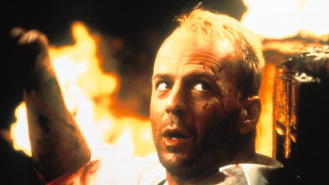 Bruce Willis vor brennendem Hintergrund.