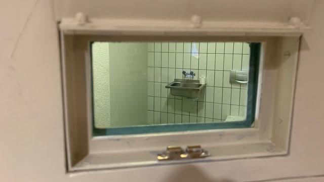 Blick durch Fensterchen in Zellentür.