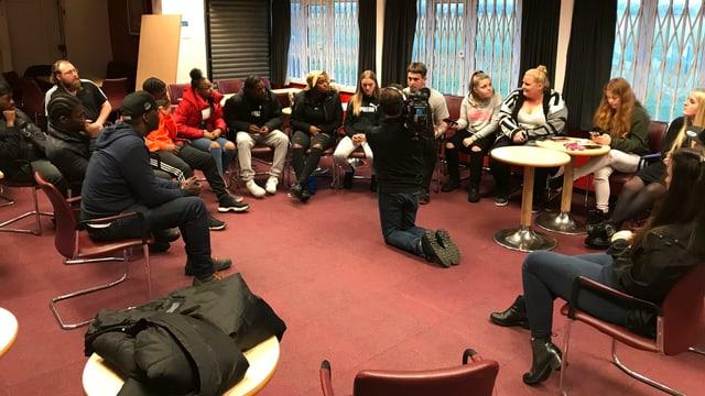 Eine Gruppe von Eltern und Jugendliche sitzen gemeinsam mit Paul in einem Kreis.