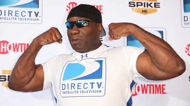 Ein Mann mit Cap und Sonnenbrille spannt seine Oberarmmuskeln an.