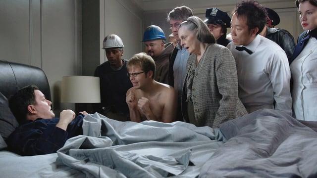 Ein Mann im Bett wird nachts im Bett von einer Gruppe toter Menschen umringt.
