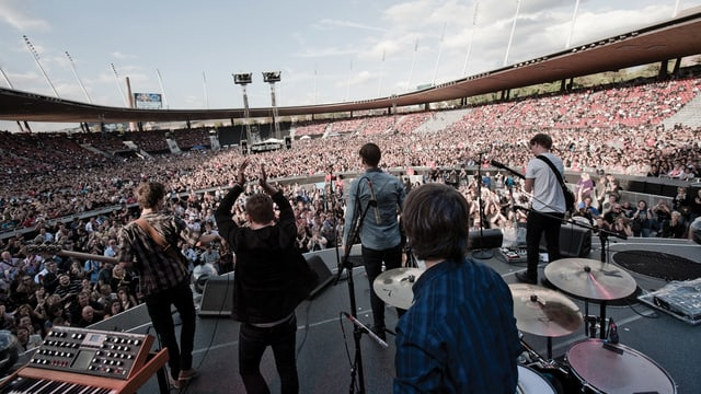 Blick von hinten auf eine Rockband, die in einem vollen Fussballstadion auf der Bühne steht.