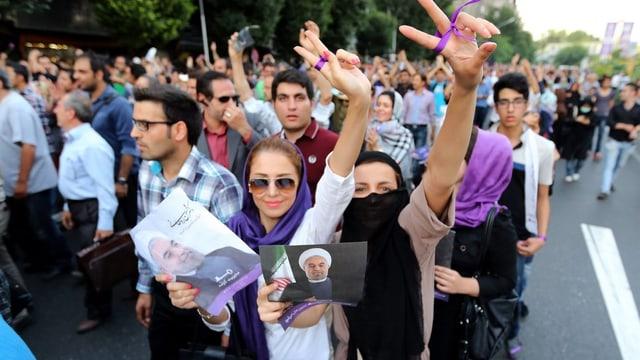 Jubelnde Menschen mit dem Foto von Rohani