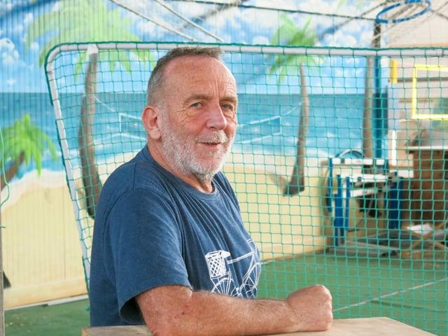 Daniel Haussener steht zwischen zwei gemalten Palmen und guckt in die Kamera.
