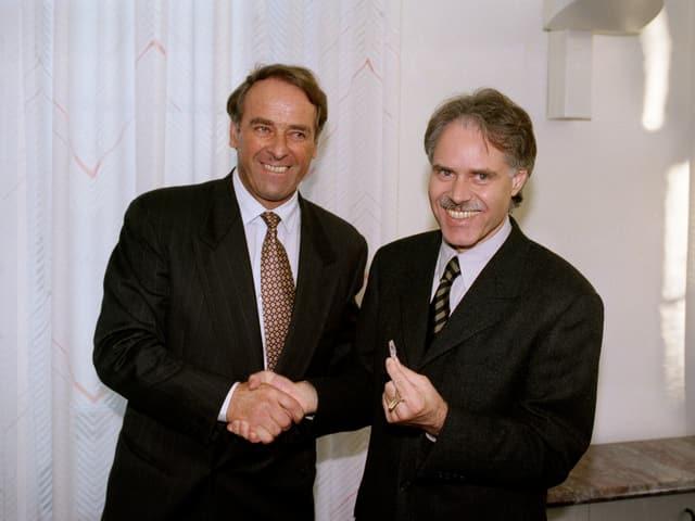Bundesräte Adolf Ogi und Moritz Leuenberger schütteln Hände.