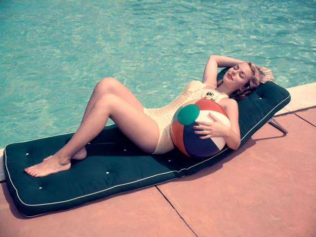 Frau in Badekleid liegt auf Matratze neben Pool