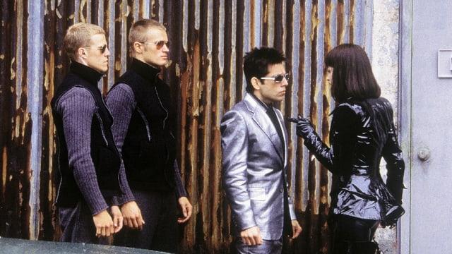 Ein Mann in schillerndem Anzug spricht mit einer Frau, dahinter stehen zwei Bodyguards.