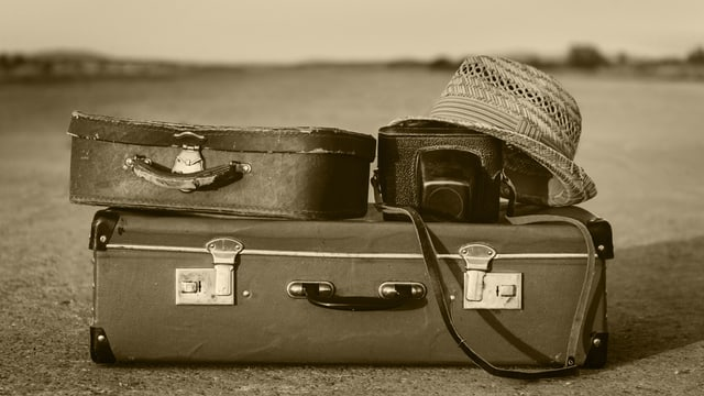 Zwei alte Koffer, eine alte Fotokamera und ein Strohhut auf einer Strasse.