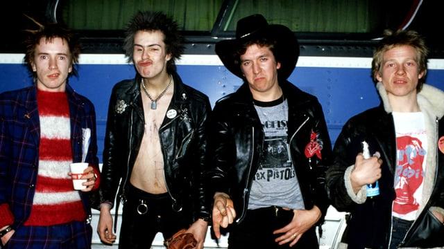 Die Bandmitglieder der Sex Pistols, vor dem Tourbus stehend und Grimassen schneidend.